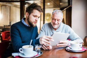 Father and son looking at a tablet screen